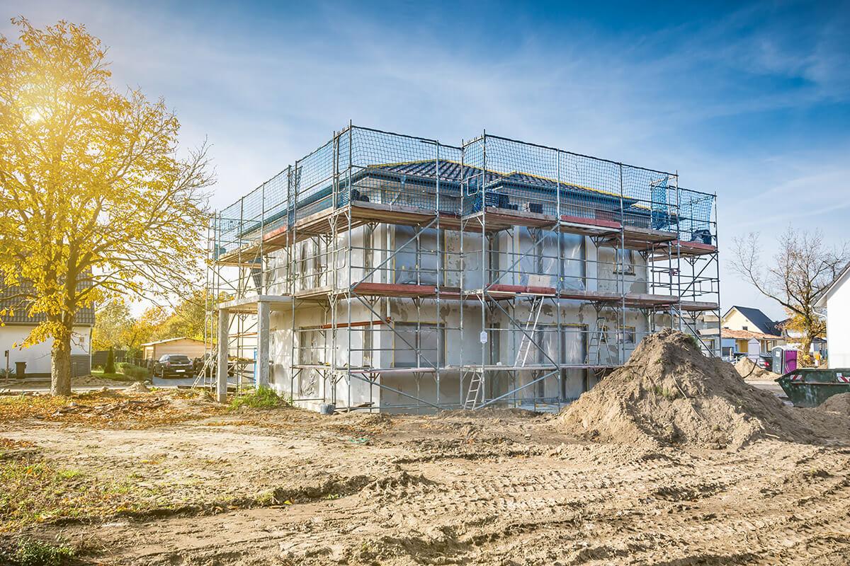 Haus mit Baugerüst wird für Fassadenrenovierung vorbereitet.